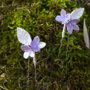 Horquilla de flores violeta y hoja blanco nacarado. Preciosa horquilla de pelo con 2 flores de color violeta y una hoja de color blanco nacarado ideal como adorno sencillo para el pelo.