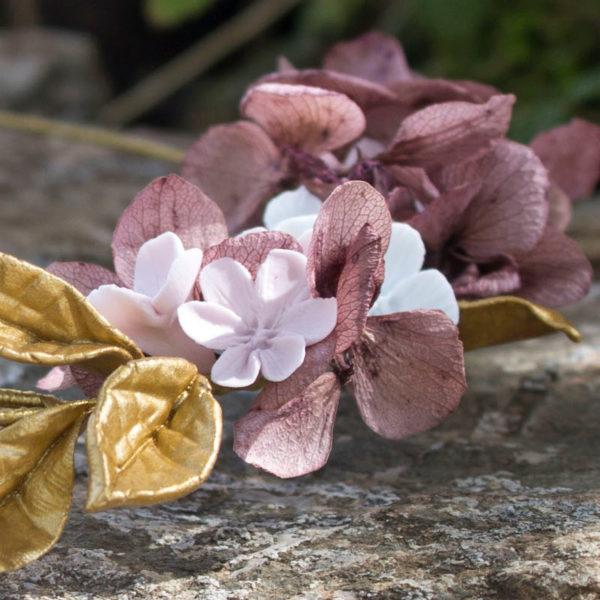 Semi corona de flores rosas y blancas y hojas de color dorado