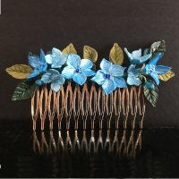 Expendido diseño de peinecillo dorado con flores azules y hojas verdes de 2 tonalidades.