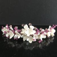 """Gran tiara de flores y pistilos de porcelana fría en tono blanco nacarado, 100% hechos a mano. Con cristal checo transparente en tono rosa maquillaje y """"paniculata"""" preservada en tono rosado, aportando dulzura para una novia única."""