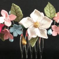 Alegre tiara de flores multicolorceleste, rosa y rosa claro, hojas en verde claro y pistilos en dorado, celeste y rosa.