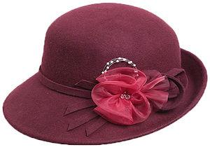 Adorno pelo invitada boda de día sombrero tipo cloche hat de color burdeos y adornos de flor roja en sinamay con bloche central de cristales checos y lazo del mismo material del sombrerito en color burdeos también.