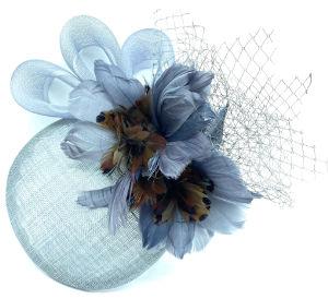 Plato o casquete de sinamay celeste con plumas de color azul y marrón, con redecilla o velo azulado y lazo en sinamay del mismo tono.