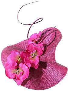 Tocado irregular en color fucsia de sinamay moldeado de manera imaginativa y elegante adornado con flores del mismo tono y con una ramita retorcida de color marrón oscuro.